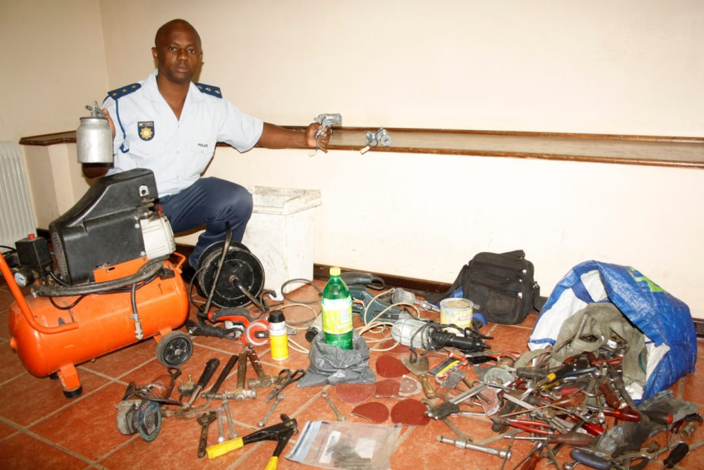 Captain Geoff Ngcobo, Acting Station Commander, with the seized car-breaking implements and equipment