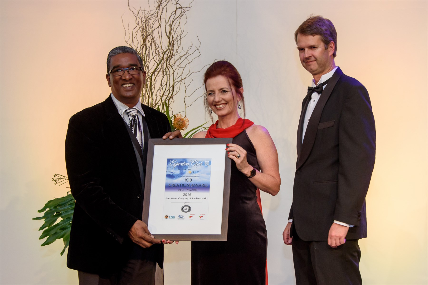 Basil Raman (Operations Manager, Ford Struandale Engine Plant) receives the Job Creation Merit Award from Jane Stevenson (Director, Magnetic Storm) and Quintin Levey