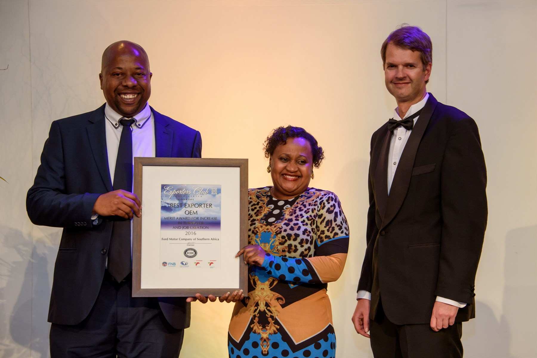 Thabo Masete (HR Manager, Ford Struandale Engine Plant) receives the Best Exporter OEM Merit Award from Colleen Siwisa (Coordinator: Investment Missions at Eastern Cape Development Corporation) and Quntin Levey